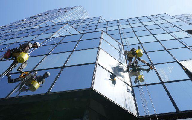 Limpiadores con arnés de seguridad limpian los cristales de un rascacielos en el centro de Varsovia
