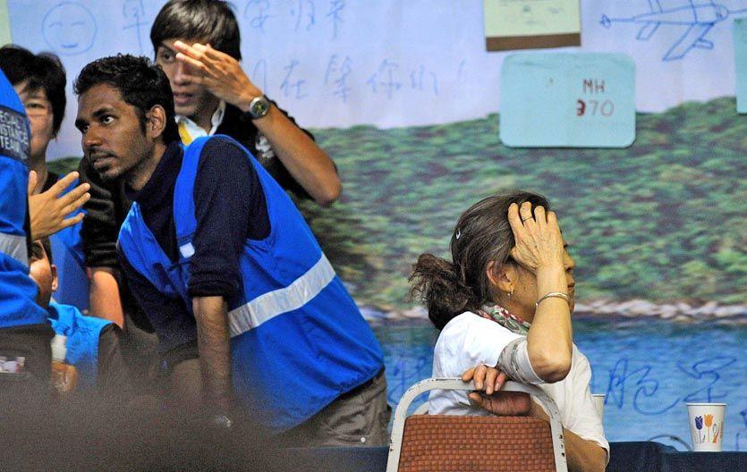 La espera continúa. Una familiar de un pasajero del vuelo de Malaysia Airlines junto a empleados de la aerolínea.
