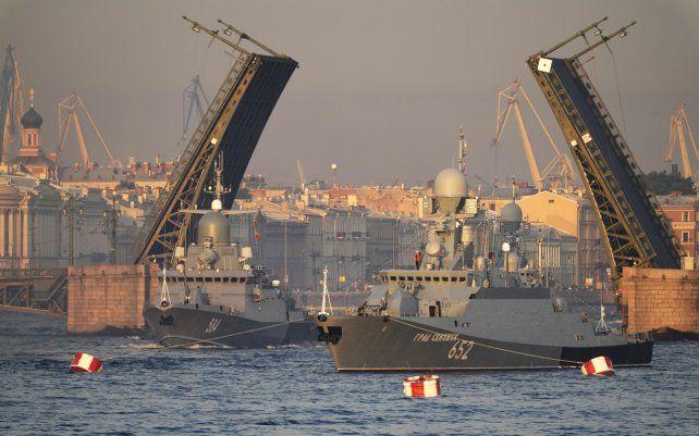 Un buque de guerra navega por el río Neva y cruza el puente levadizo Dvortsovy que se eleva sobre el río durante un ensayo del desfile naval en San Petersburgo