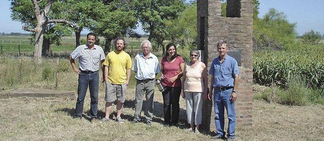 Posta de Arequito. El jefe comunal y miembros del Ferroclub junto al monolito.