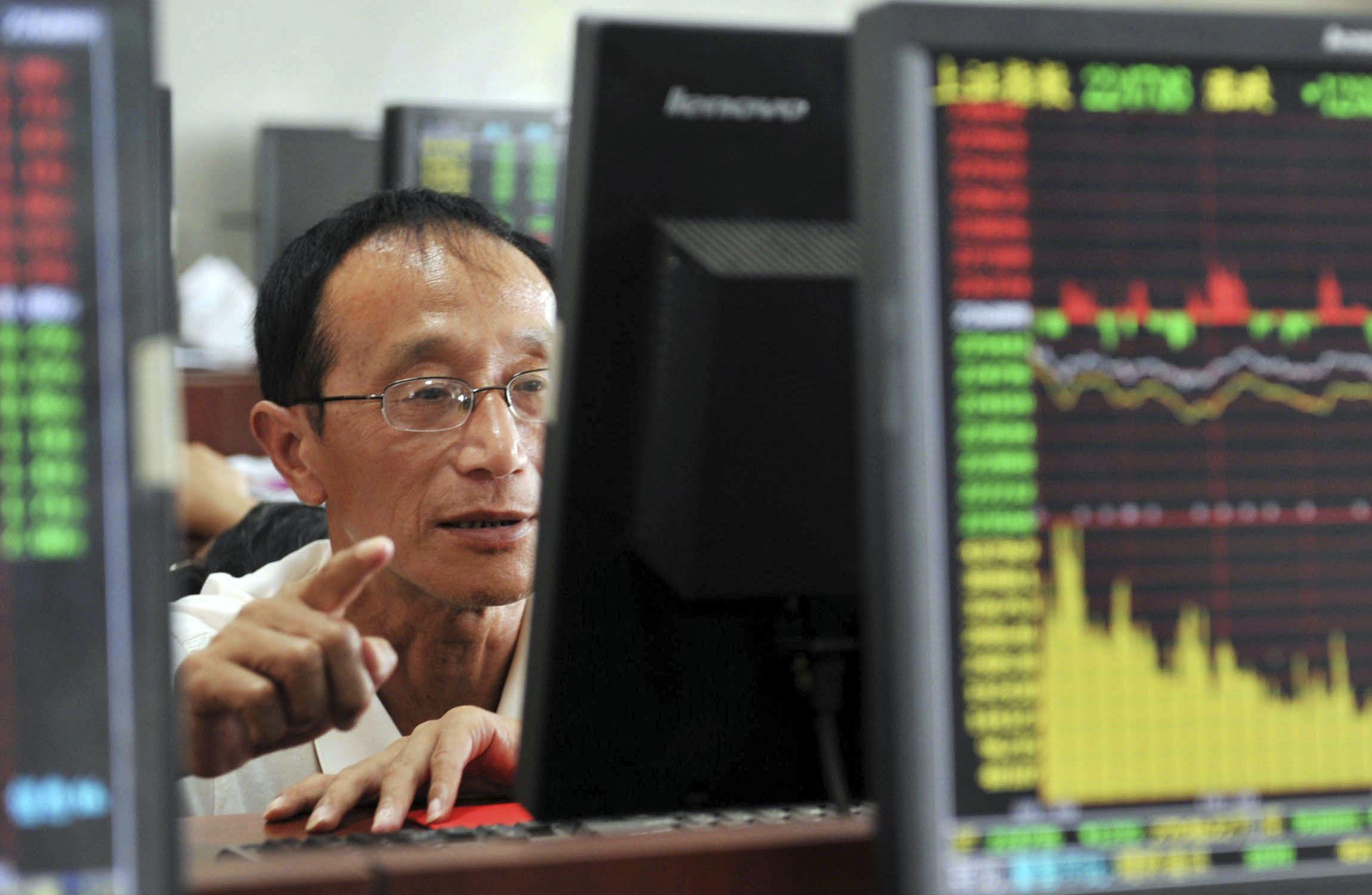 En baja. Un operador de la Bolsa de Shanghai asiste a una nueva caída de esa plaza bursátil. Otro día de tensión.