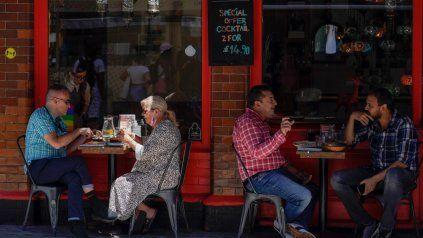 LONDRES. Clientes sentados en la vereda en un bar del Soho londinense. En Gran Bretaña el 95% de los casos son variante Delta.