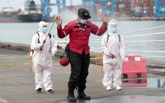 Miembros de la Cruz Roja Indonesia rocían a un socorrista con desinfectante después de clasificar partes de aviones y escombros recuperados del mar de Java