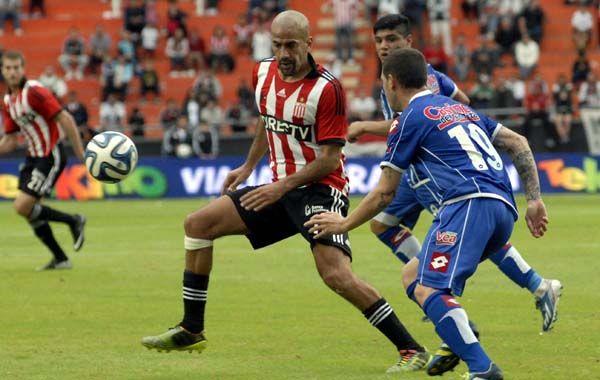 Con clase. Verón intenta dominarla ante el acoso de José Luis Fernández. El Pincha erró chances y lo pagó caro.