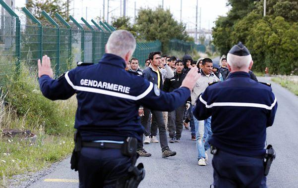 Fuga desesperada. Gendarmes franceses intentan detener a refugiados que intentan escapar hacia Gran Bretaña.