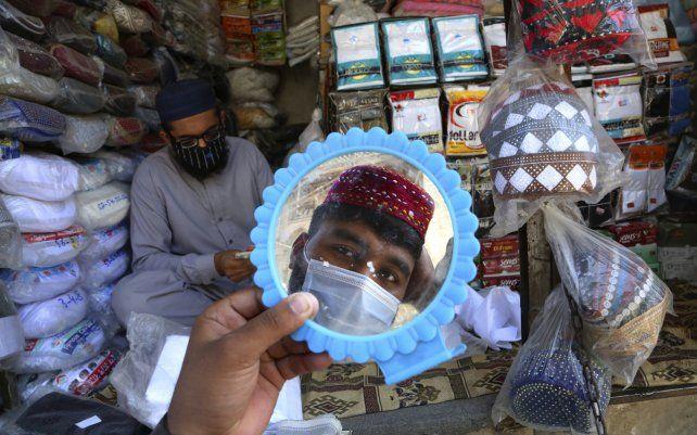Un hombre se prueba un gorro tradicional en preparación para el próximo mes de ayuno musulmán del Ramadán, en Peshawar, Pakistán. Los musulmanes suelen aumentar sus actividades religiosas durante el Ramadán, que comienza probablemente con la luna nueva la semana próxima.