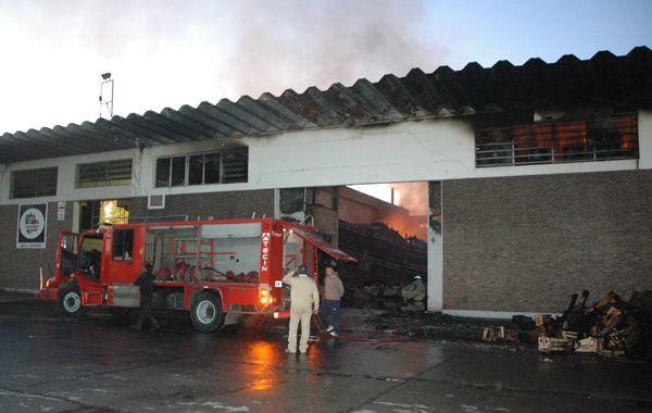 Bomberos trabajan frente al galpón incendiado esta tarde