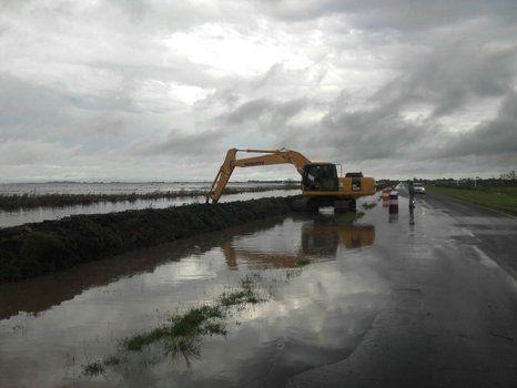 Obras ante el peligro. Una excavadora refuerza el terraplén de la ruta 90 en la zona de la laguna