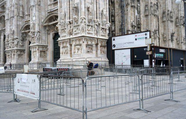 Duomo. Un turista con barbijo de pie junto a la entrada cerrada de la catedral de Milán.