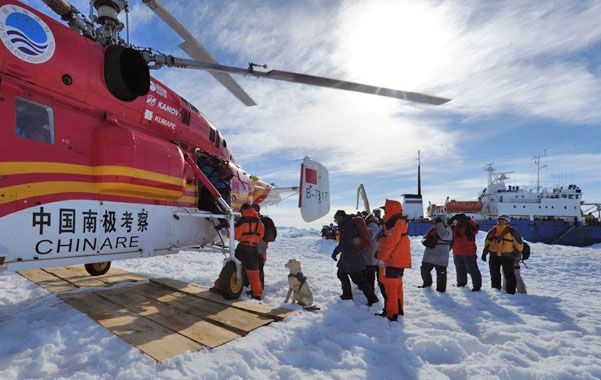 A salvo. Los pasajeros suben al helicóptero. Atrás