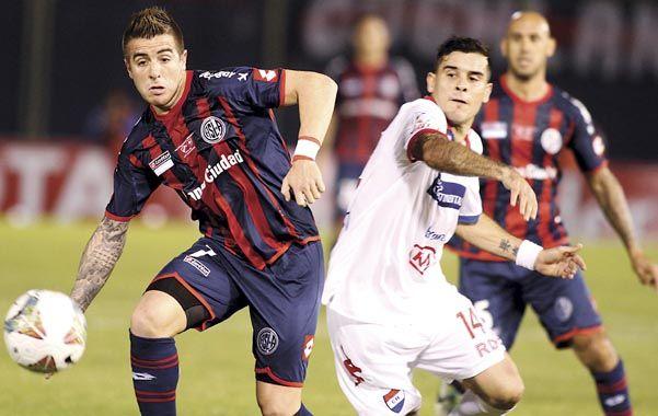 Buffarini disputa el balón con Melgarejo. San Lorenzo definirá la Copa el próximo miércoles.