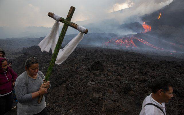 Una mujer lleva una cruz durante una peregrinación para rezar para que el volcán Pacaya disminuya su actividad en San Vicente Pacaya