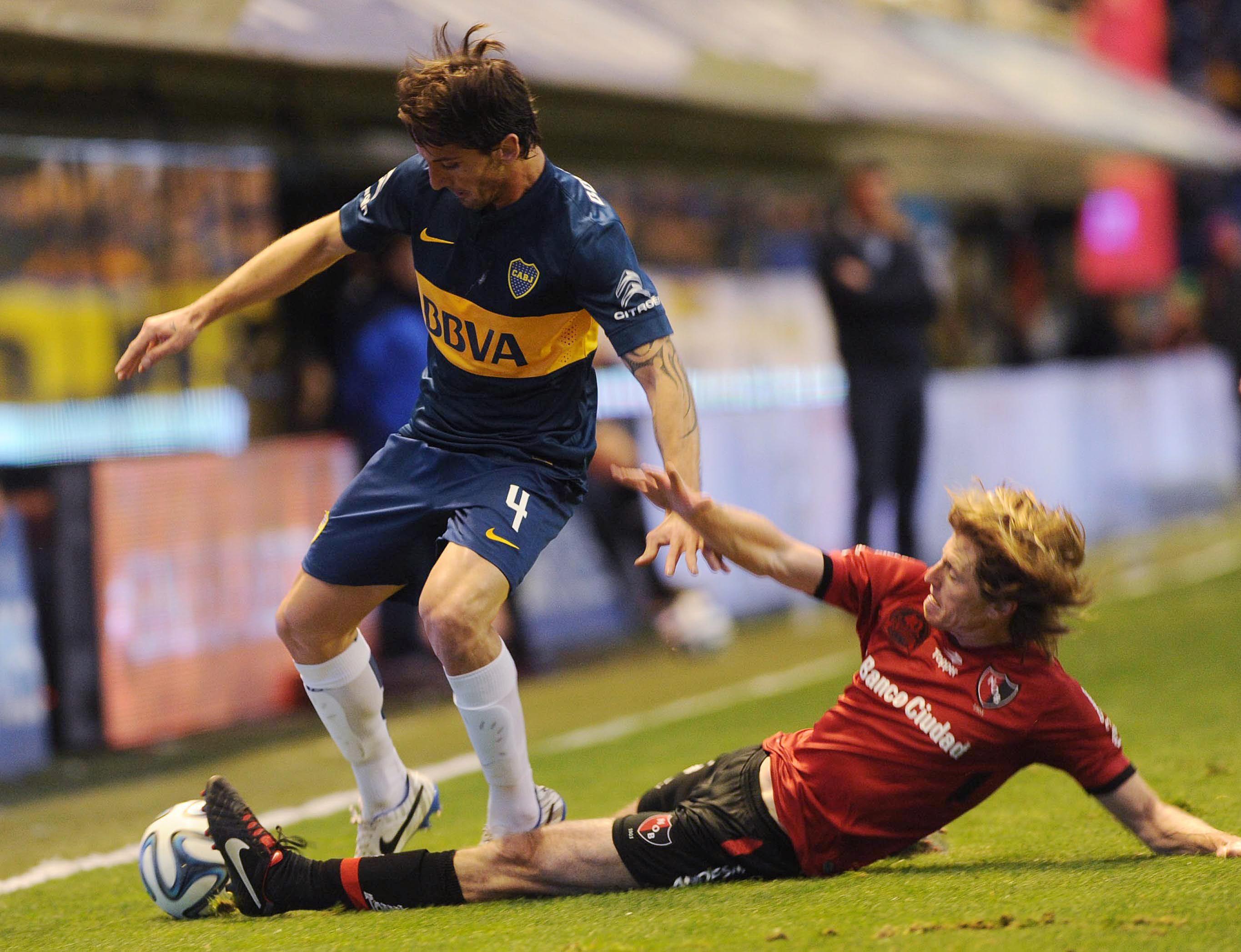 Pomelo Mateo va al piso para tapar la subida de un jugador de Boca.