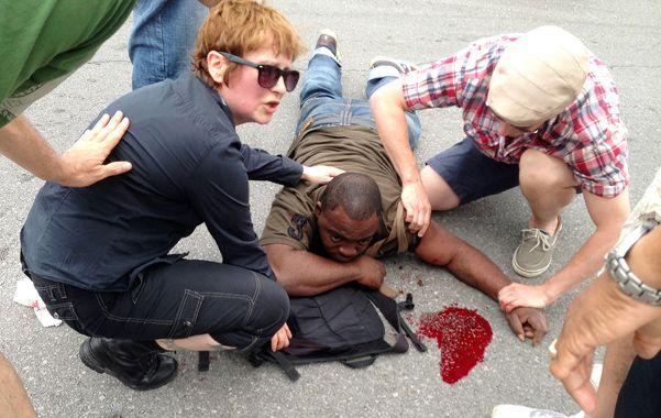 Espectadores asisten a un herido de bala mientras esperan la llegada de las ambulancias.