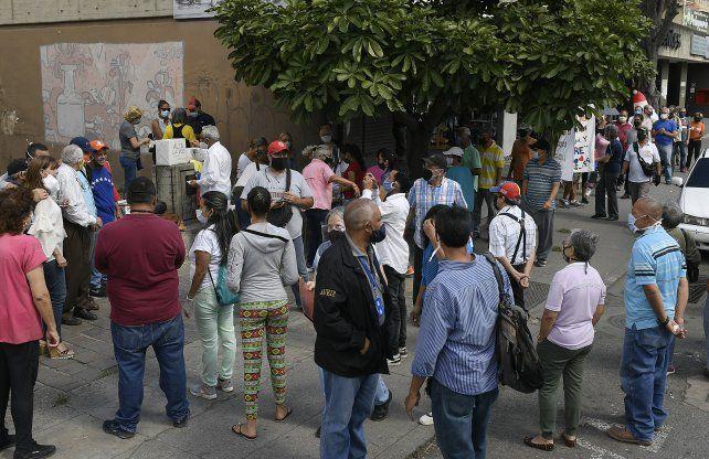 Una nutrida fila de ciudadanos espera para votar en una mesa improvisada en un barrio de Caracas.