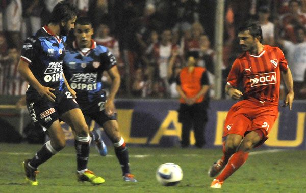 Emiliano Papa trata de progresar ante dos jugadores de Unión. (Foto: NA)