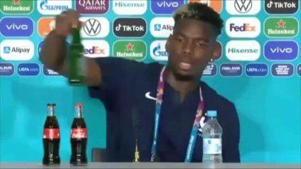 El jugador Pogba retira de la mesa de la conferencia de prensa el envase de una marca de cerveza que patrocina la Eurocopa.
