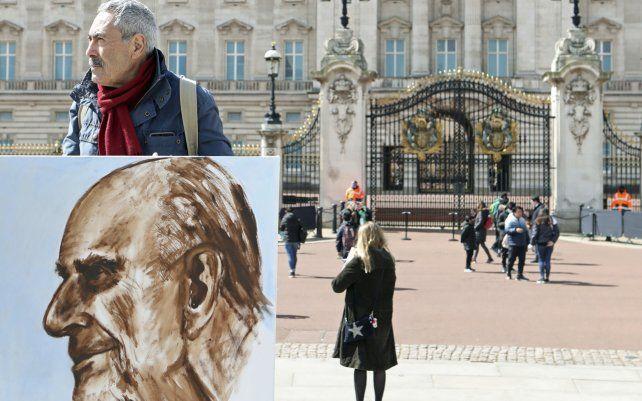 El artista Kaya Mar sostiene un retrato que pintó del duque de Edimburgo frente al Palacio de Buckingham. El príncipe Felipe de Gran Bretaña