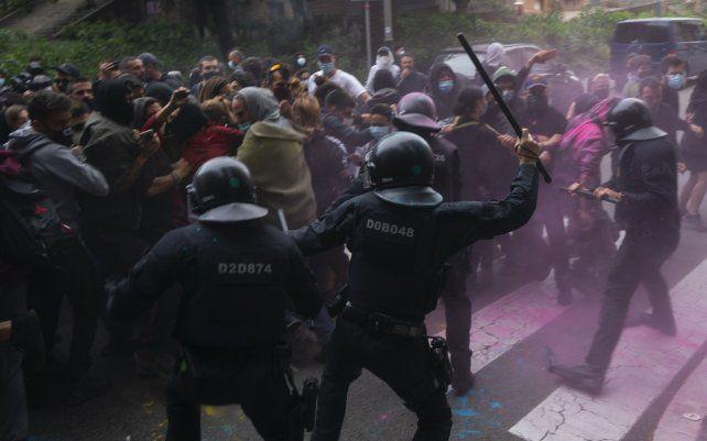 Agentes de policía de Riot usan sus bastones para dispersar a los manifestantes que intentan detener el desalojo de Axel Altadill
