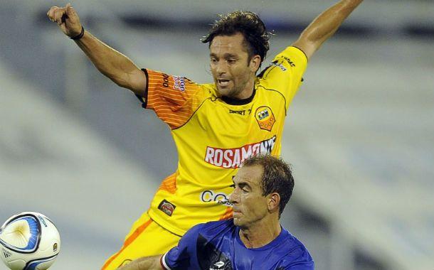 En el aire. Diego Torres disputa la pelota con el volante de Vélez Somoza.
