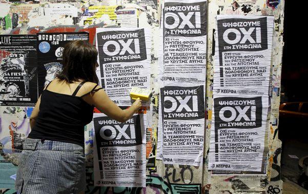 """""""No"""".  Una militante de Syriza pega carteles en Atenas que llaman a votar """"no"""" (""""Oxi"""") el próximo domingo."""