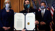 La presidenta de la Cámara de Representantes, Nancy Pelosi, muestra el pedido de juicio firmado.
