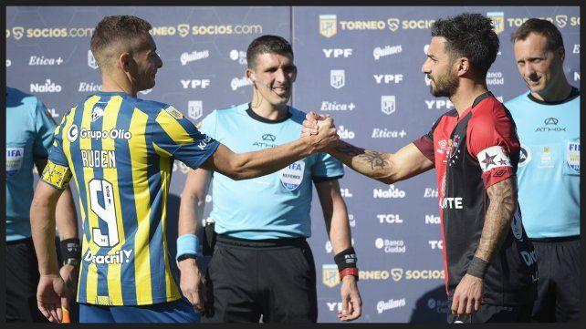 Marco Ruben y Nacho Scocco se saludan con el puño tras el sorteo inicial. La imagen refleja la paridad del resultado final.