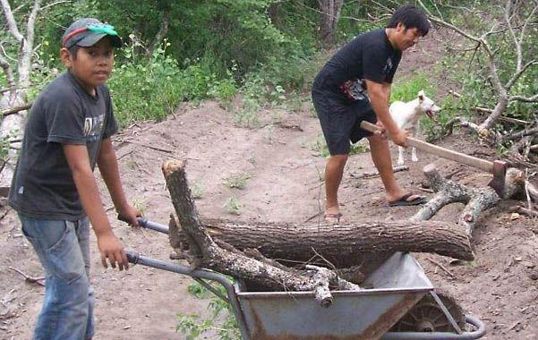 La imagen muestra a Iber Flores junto a su tío Oscar Talero en los trabajos de la comunidad qom.