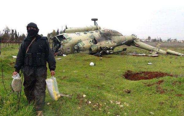 Victoria. Un rebelde se exhibe ante los restos de un helicóptero pesado.