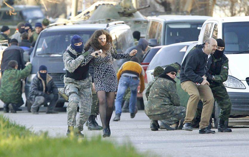 Civiles son ayudados por fuerzas prorrusas a salir de la base aérea ucraniana de Belbek.