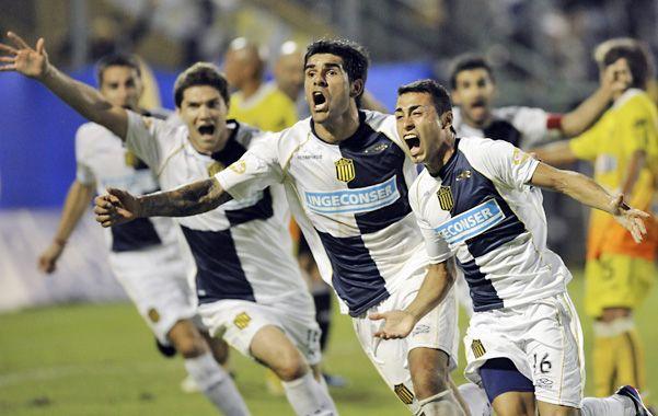 Pachi Carrizo sale corriendo eufórico porque acaba de marcar el gol del triunfo canalla. Detrás aparece Toledo