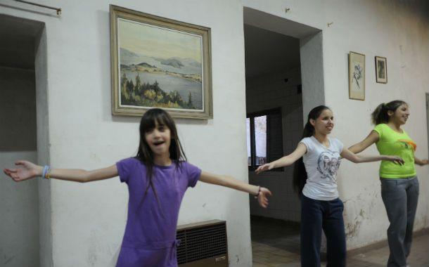 Tres chicas no videntes bailan y se divierten en el grupo de danzas.