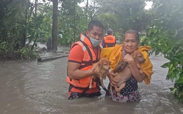 Un rescatista ayuda a una mujer a llevar a sus cachorros a lo largo de las inundaciones causadas por la tormenta tropical Conson en Naic, provincia de Cavite, Filipinas. El tifón Conson azotó el miércoles el este de Filipinas.