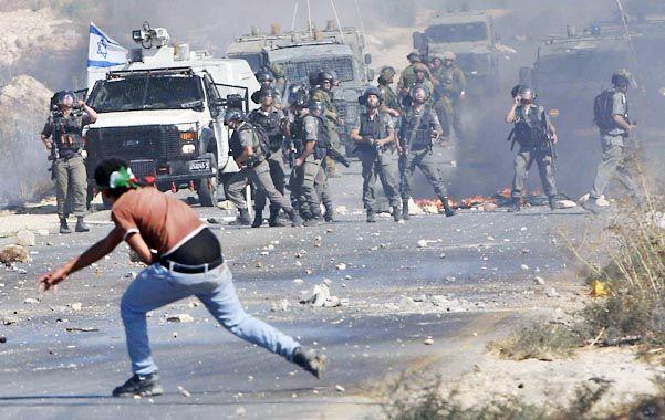 Protesta. Un militante palestino arroja piedras hacia unos soldados israelíes en un control militar en Cisjordania.
