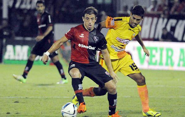 En cancha. El Cabezón Bernardello cuida la pelota ante la marca del volante Fabio Vázquez