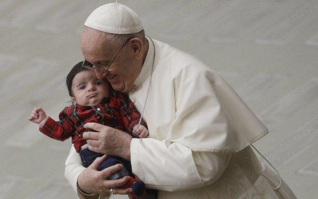ARCHIVO - El Papa Francisco abraza a un bebé mientras intercambia un saludo navideño con los empleados del Vaticano en el salón Pablo VI. El Vaticano ha confirmado que el Papa Francisco recibió la primera inyección de la vacuna anti-COVID este jueves.
