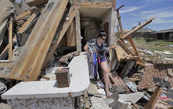 En ruinas. Una joven rescata algo de ropa de su ex dormitorio