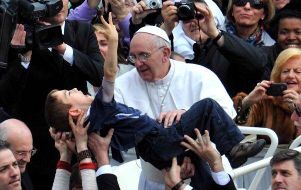 Francisco sostiene a un niño con discapacidades en la asunción.