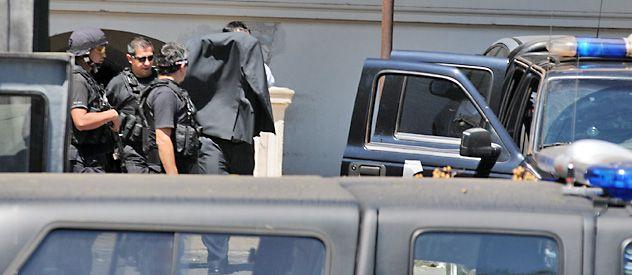 El comisario Néstor Juan Fernández sale de los Tribunales Federales oculto tras el saco de su traje. (Foto: Sergio Torigino)