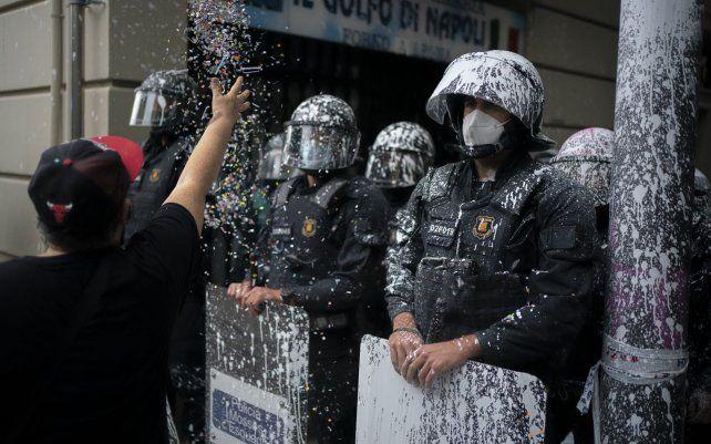 Agentes antidisturbios cubiertos por pintura arrojada por los manifestantes