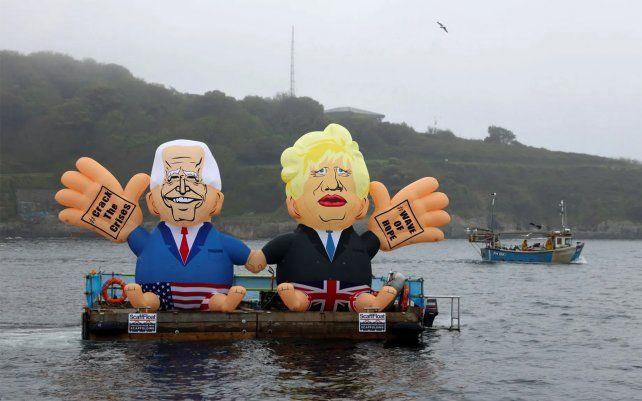 Muñecos inflables que representan al presidente Biden y Boris Johnson se muestran en un bote en la playa de Gyllyngvase en Falmouth. Fotografía: Tom Nicholson / Reuters