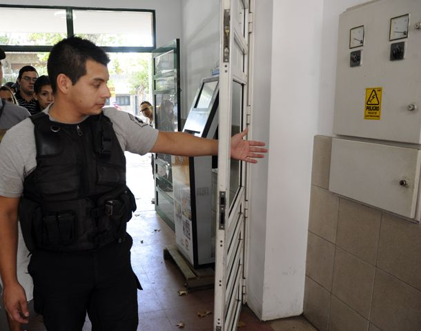 Un policía muestra cómo quedó la puerta de la guardia del Carrasco. (Foto: S. Toriggino)