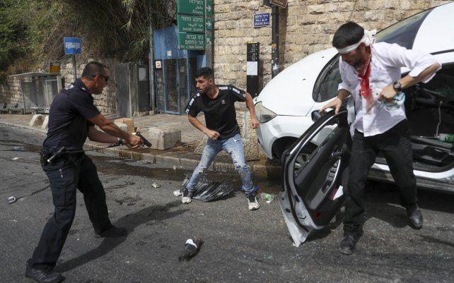 Un oficial de policía israelí apunta con una pistola a un hombre palestino