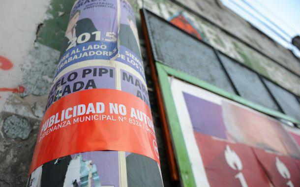Se observan afiches instalados sobre cestos y columnas de alumbrado
