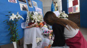 Una compañera de Ticiana le rinde su homenaje en el altar levantado en la puerta de la escuela a la que concurría.
