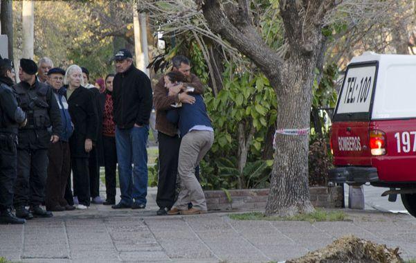 Dolor. Vecinos y familiares de la familia Palacios lloraban abrazados en la vereda mientras los bomberos y la policía retiraban los cuerpos de las víctimas.