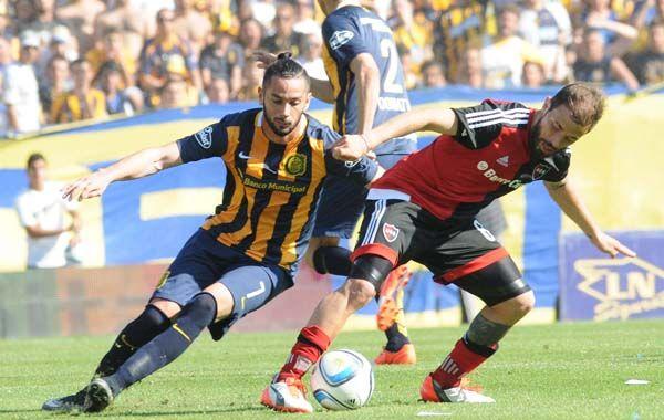 Hernán Bernardello se anticipa a Marcelo Larrondo. El clásico terminó con una pobre igualdad.
