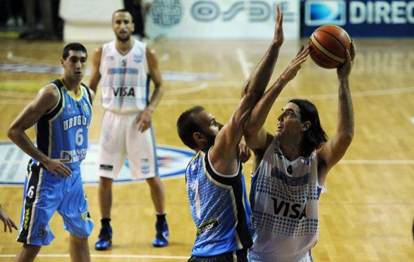 Luis Scola busca lanzar al aro pese a la oposición de Kiril Wachsmann. (Foto Matías Sarlo)