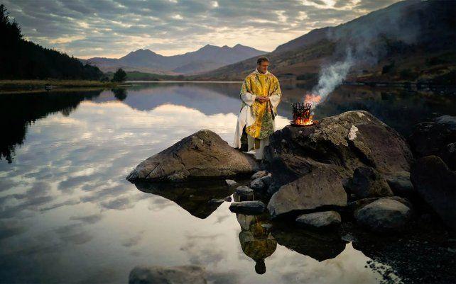 El reverendo Stuart Elliott bendice el nuevo fuego como parte de su Servicio de Nueva Luz para la víspera de Pascua en la costa de Llynnau Mymbyr en Snowdonia