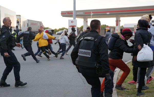"Escape. Gendarmes franceses intentan contener a un grupo de ""sin papeles"" que intenta cruzar el Eurotúnel."